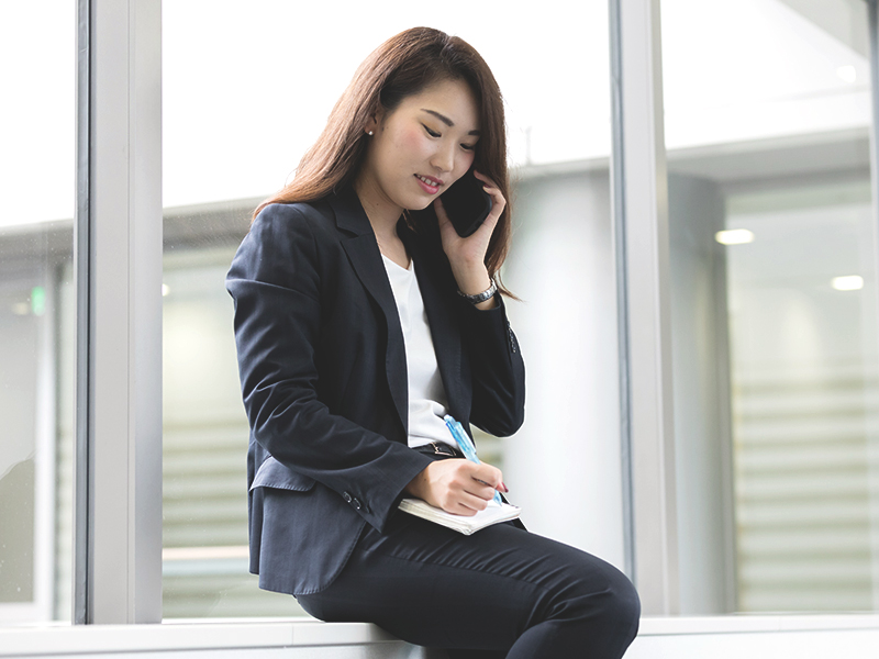 新人営業が、スケジュール帳を片手に訪問のアポイントを打診中。<br>スケジュールを埋めるのも新人営業の大事な仕事。それらを成果に結びつけられるように経験を積んでいきます。