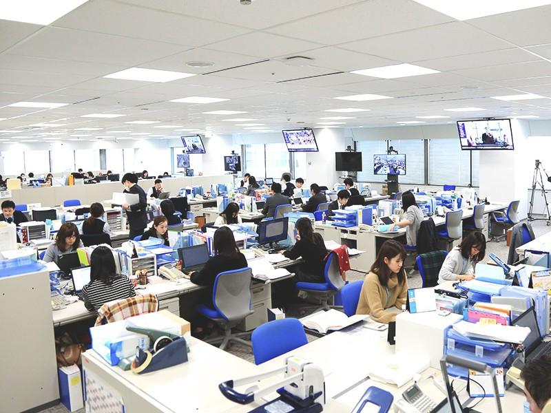 東京本社のオフィスフロアの風景です。<br>パーティションなどの仕切りがない開放的な環境で、営業部や販促企画部、総務、リクルーティンググループなど、さまざまな部門が一緒に働いています。